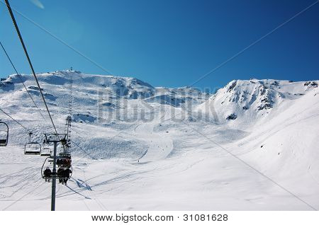 skiers on long slopes in Alps