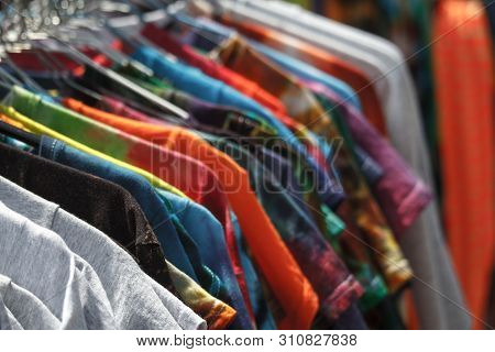 Close-up Of Multi-colored T-shirts Hanging On Hangers In The Street, Fair, Secondhand, Recycling Con