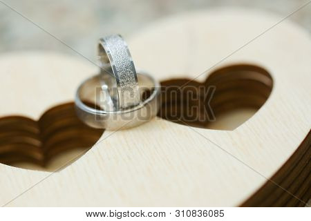 Two Wedding Rings On Wooden Case In Heart Shape. Close Up Macro Shot Of Silver Rings