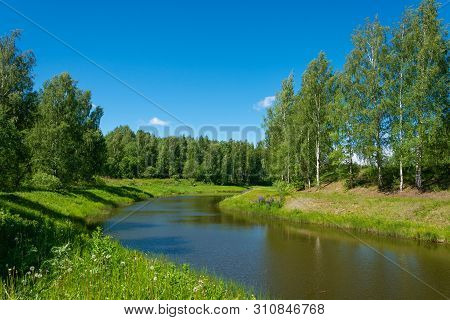 A Small Water Channel With Green Beaches And Birch Groves.