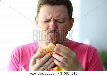 Portrait Of Unsatisfied Male Eating Tasteless Hamburger With Obvious Disgust. Bearded Person Holding