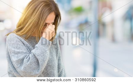 Beautiful middle age woman wearing winter sweater over isolated background tired rubbing nose and eyes feeling fatigue and headache. Stress and frustration concept.