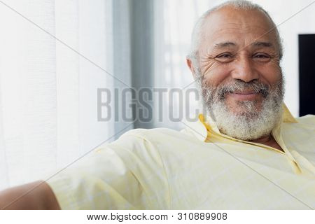 Portrait close up of senior mixed race man smiling inside room. Authentic Senior Retired Life Concept