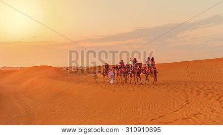 Dubai, Uae - November 09, 2018: Desert Safari Tourists Riding Camels - Travel Concept With People On