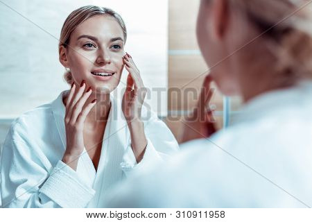 Calm Blonde Woman Touching Her Face And Checking State Of The Skin