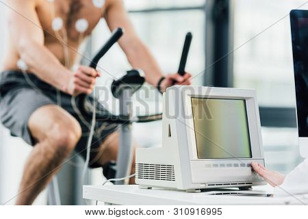 Cropped view of sportsman with electrodes training on elliptical during endurance test in gym poster