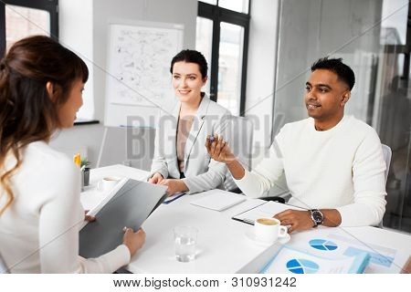 new job, hiring and employment concept - international team of recruiters having interview with female employee at office