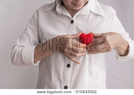 Smiling Asian Elderly Woman Holding Red Heart Shape, Concept Of Prevention Heart Disease, Front View