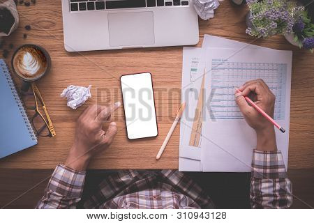 Wood Office Table With Businessman Checking Report Paper, Blank Screen On Mobile, View From Above Ta