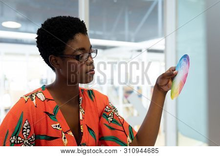 Side view of young African american female graphic designer looking at color swatch in office. This is a casual creative start-up business office for a diverse team poster