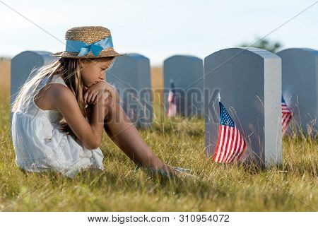 selective focus of sad child sitting and looking at headstones with american flags poster