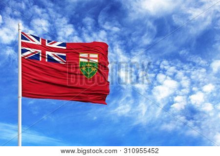 National Flag Of Ontario On A Flagpole In Front Of Blue Sky