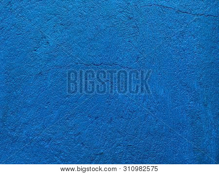 Old navy blue wall covered with shabby uneven plaster. Texture of vintage turquoise stone surface, closeup. poster