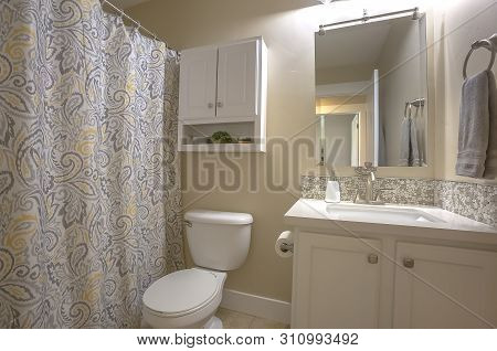 Toilet Vanity Mirror And Cabinet Inside Bathroom With Beige Wall And Tile Floor