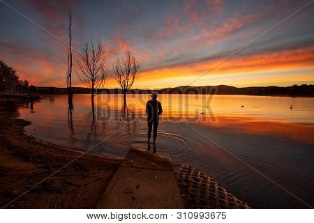 A Traveller Watching The Beautiful Colourful Sky And Reflections On Lake Jindabyne In The Snowy Moun