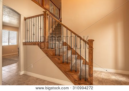Carpeted Stairs With Wood Handrail And Metal Railing Inside An Empty New Home