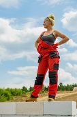 Woman wearing workwear on construction site. Female takes break from work, standing on wall against blue sky. Partially built new house early stage. Industry. poster