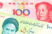 A close up image of a green Iranian ten thousand rial bank note with a red, one hundred yuan Chinese renminbi note in macro poster