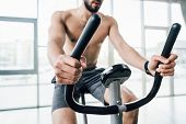 partial view of sportsman training on elliptical machine at gym poster
