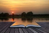 Creative concept of beautiful simple image of sunset through tress reflected in lake in foreground coming out of magical book laid open poster