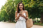 Portrait of lovely woman in summer dress smiling and holding cellphone while walking through green boulevard poster