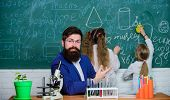 Explaining biology to children. How to interest children study. Fascinating biology lesson. School teacher of biology. Man bearded teacher work with microscope and test tubes in biology classroom poster