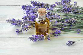Lavender Essential Oil In A Glass Bottle With A Bouquet Of Fresh Blooming Lavender Flowers On A Rust