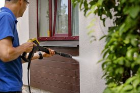 House Facade Cleaning Service. Man Washing Wall With High Pressure Washer