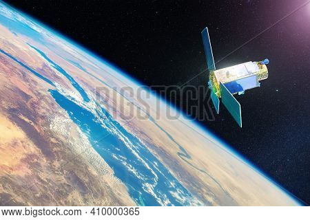Communication Satellite And Research Equipment In Earth Orbit, Flies Through The Deserts Of Africa A