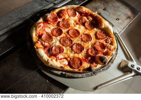 Freshly Made Pepperoni Pizza, Coming Out Of The Oven Of A Pizzeria With Shovel.