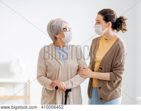 Adult daughter and senior parent wearing facemasks during coronavirus and flu outbreak. Help for the convalescent.
