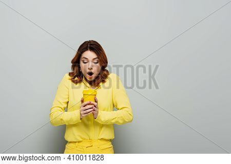 Shocked Woman In Yellow Blouse Holding Hot Coffee In Yellow Paper Cup On Grey.