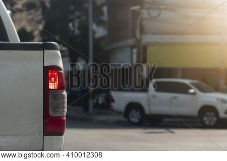 Rear Side Of Used Pickup Car White Color With Open Brake Light. Stop And Park On The Road Before Cro