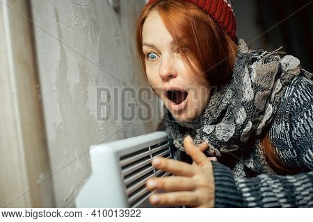 Emotional Woman Warms Up At The Radiator In A Cold House, Problems With Heating, Heating The Room Wi