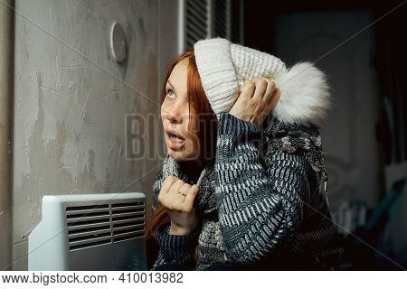 A Woman Is Warming Herself At The Radiator In A Cold House, Problems With Heating, Heating The Room