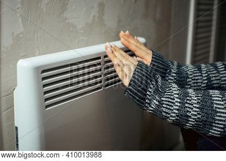 A Woman Warms Her Hands At The Radiator In A Cold House, Problems With Heating, Heating The Room Wit