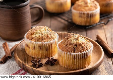 Two Cinnamon Muffins On A Wooden Plate With Cup Of Coffee And Muffins On A Rack In Background