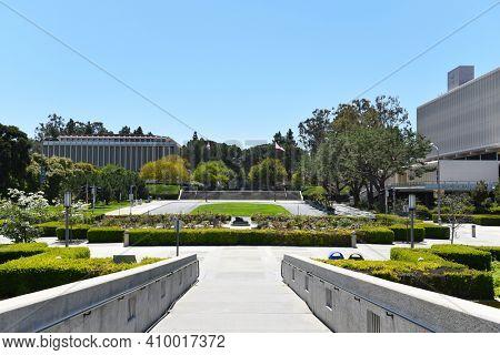 IRVINE, CALIFORNIA - 16 APRIL 2020: Wastson Bridge looking towards the campus of the University of California Irvine, with the Laurel L. Wilkening Rose Garden.