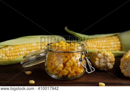 Tasty Sweet Corn Kernels In Jar And Fresh Cobs On Wooden Table