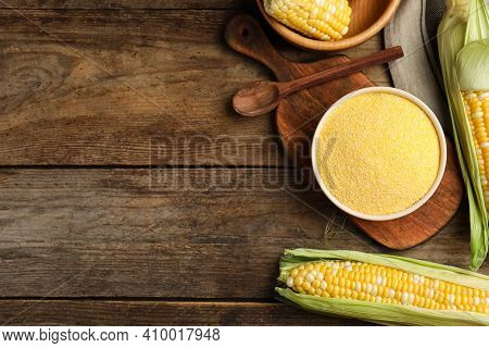 Cornmeal In Bowl And Fresh Cobs On Wooden Table, Flat Lay. Space For Text