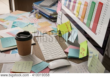 Computer, Notes And Office Stationery In Mess On Desk. Overwhelmed With Work
