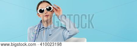 Trendy Woman In Blouse Adjusting Sunglasses While Posing Isolated On Blue, Banner