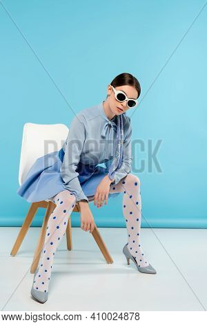 Glamour Woman In Dotted Tights And Sunglasses Sitting On Blue Background