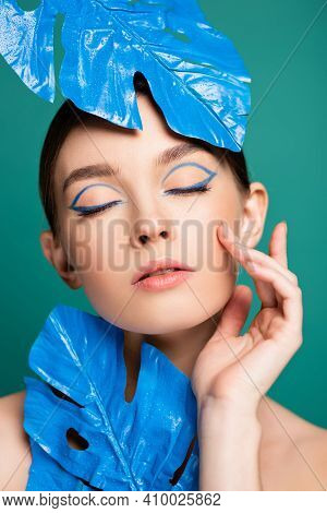Pretty Woman With Blue Eyeliner On Closed Eyes Posing Near Wet Leaves Isolated On Green