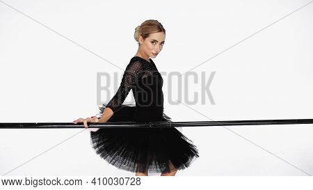 Young Ballerina In Tutu Skirt Standing Near Barre On White Background
