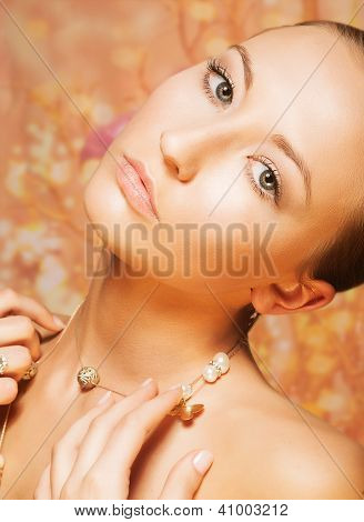 Feminine. Tenderness. Portrait Of Imposing Woman With Gold Pearly Chainlet