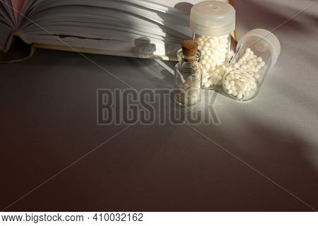 Homeopathic Granules In Storage Flasks. In The Background, A Book On Homeopathic Treatment.