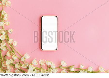 Smartphone With Blank Screen And Spring Flowers On Pink Paper Flat Lay. Floral Tender Border Of Whit