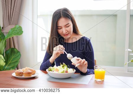 Young Asian Woman Eating Healthy Salad With Fresh Vegetable And Orange Juice On Wellness Lifestyle F