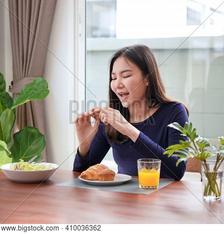 Close Up Of Young Asian Woman Holding And Have A Bit To Eating Bread With A Glass Of Fresh Orange Ju
